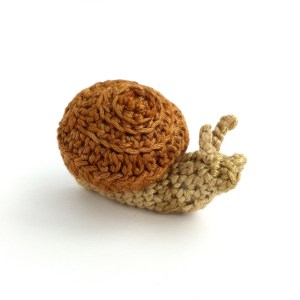 Picture of Little Conkers snail, hand-crocheted in shades of taupe and brown.
