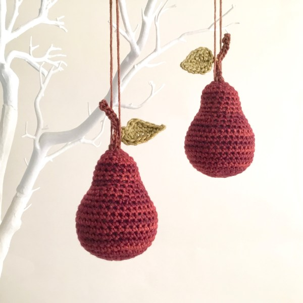 Deep red crocheted pear ornaments hanging on a twig tree