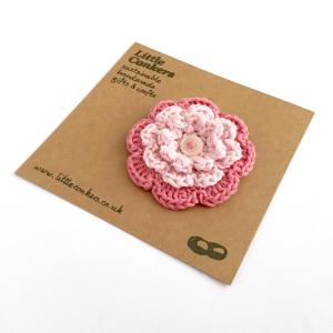 Pink crocheted flower brooch with button centre