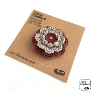 Hand-crocheted flower brooch in plum and grey with a button centre