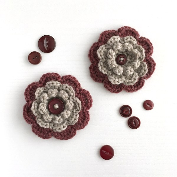 Hand-crocheted flower brooches in plum and grey with a button centre