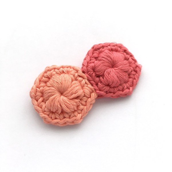 Crocheted brooch made of two hexagons in peach and pink