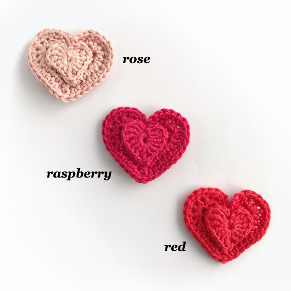 Small crocheted heart brooches in pink and red