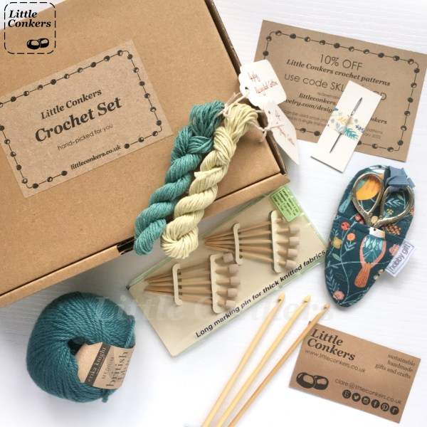 Kraft brown box containing crochet tools and yarn. Contents include large and small skeins of wool, scissors in a fabric case, crochet hooks, bamboo marking pins and yarn needle.