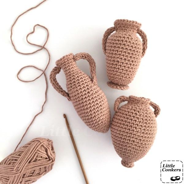 Three crocheted amphorae, yarn and a crochet hook