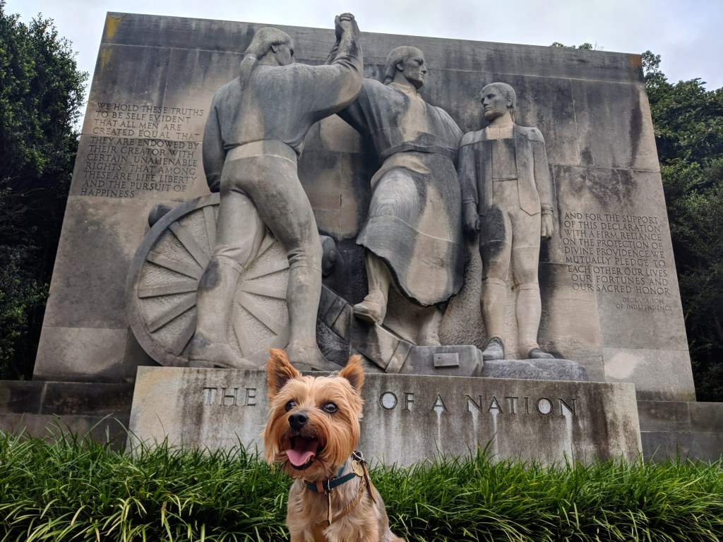 """A small dog stands in front of a large statue in Philadelphia titled """"The Birth of a Nation."""" The dog is blocking the word """"birth."""""""