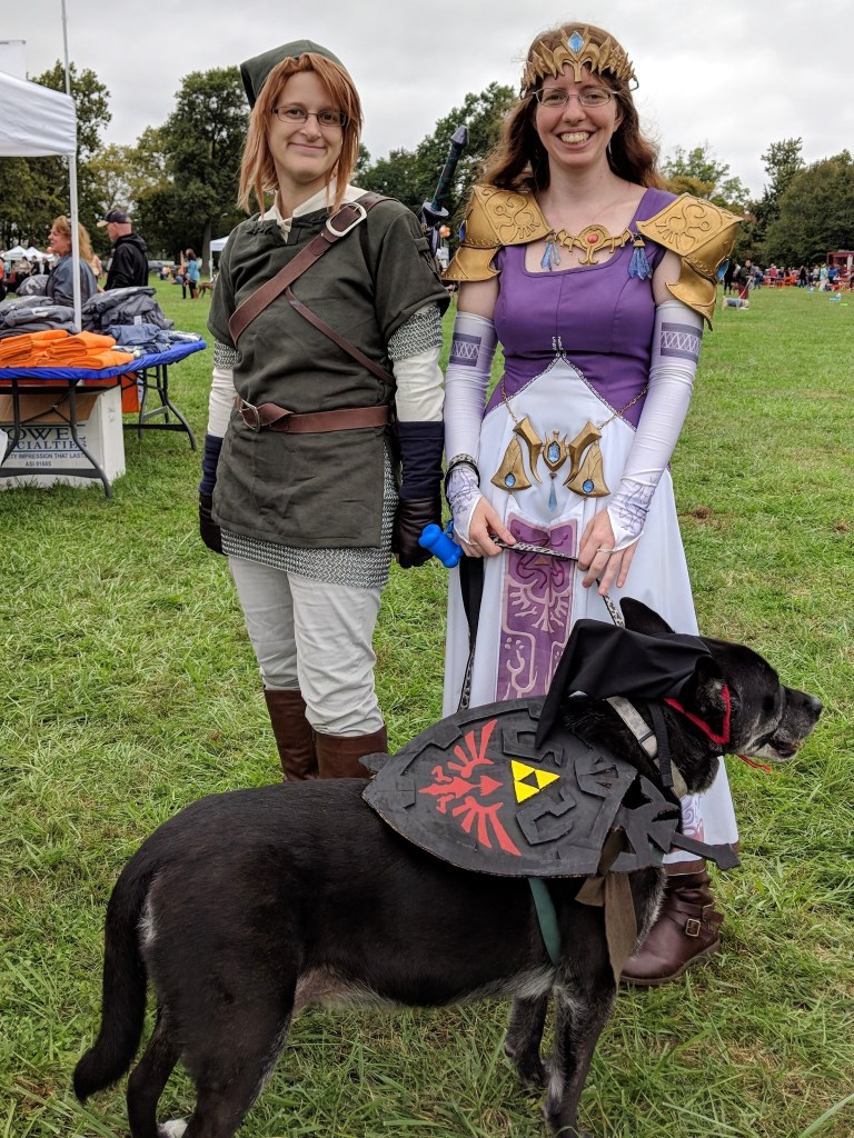 Two people stand dressed as the characters from the Legend of Zelda with their black dog. The dog is dressed as Shadow Link with a black hat and shield.