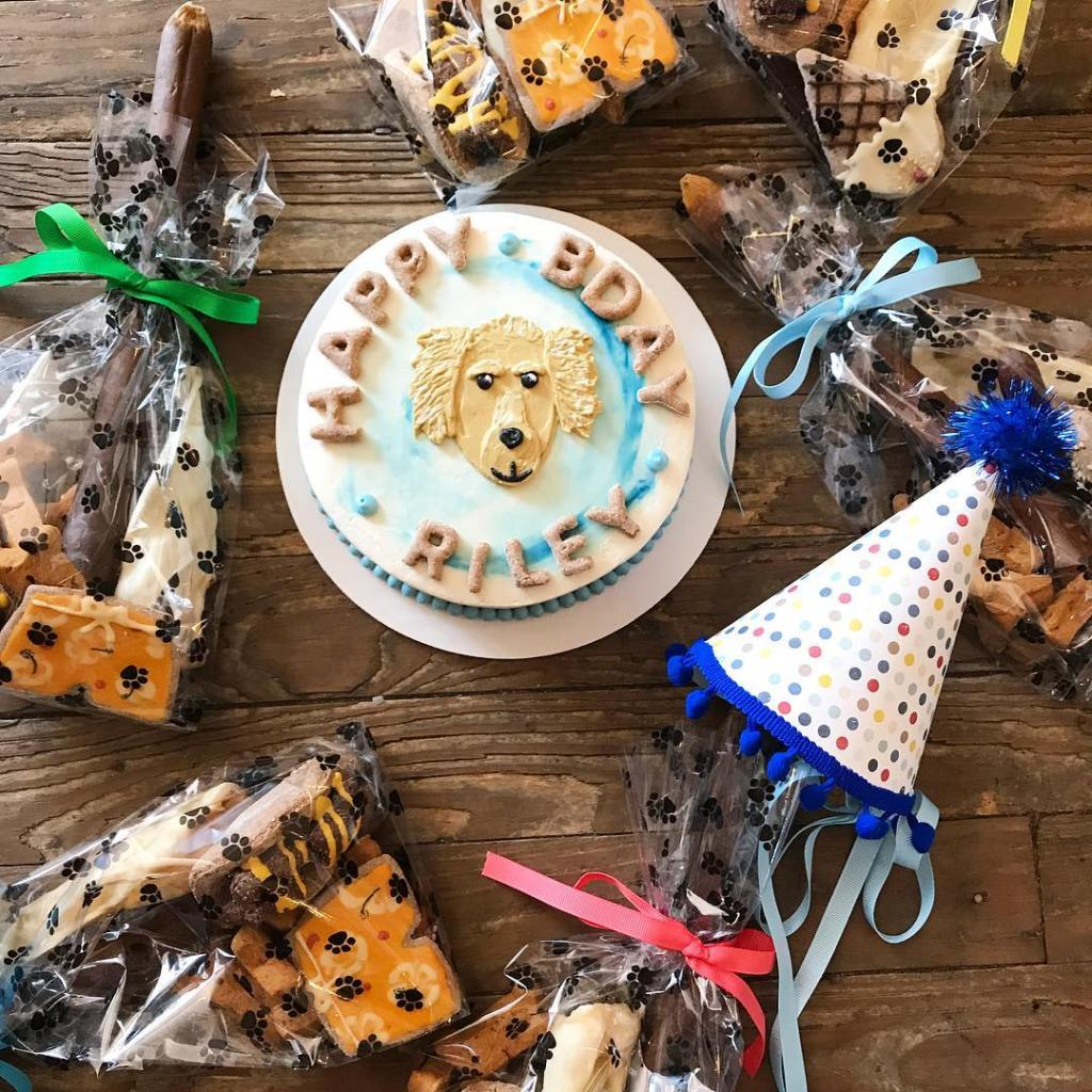 A blue and white birthday cake with dog drawn in icing in the middle sit on a wood surface surrunded by goodie bags and a birthday hat for a dog's birthday party