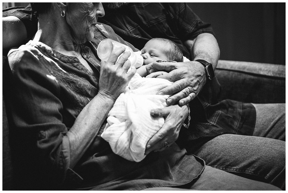 Grandparents feed baby at newborn session.