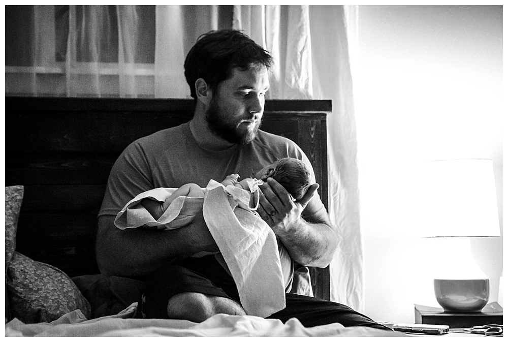 Dad holding newborn baby minutes after homebirth.