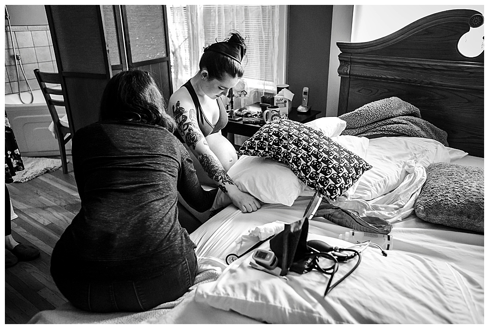 Midwife takes Devon's vital signs during labor. Birth photos by Renee Begeron of Little Earthling Photography.