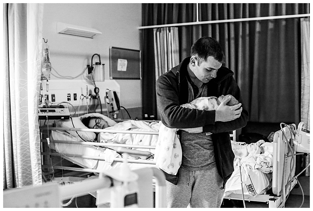 Dad holding newborn in hospital.