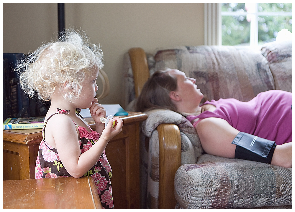 Curly-haired toddler watching her mama be examined by midwife.