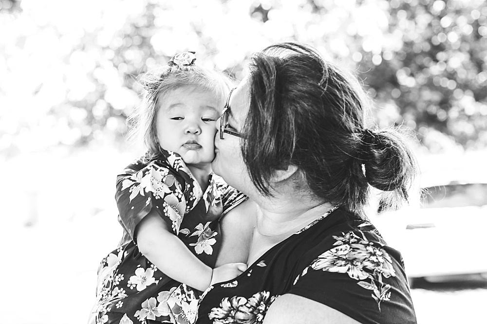 Asian mother kissing baby. Bellingham photographer Little Earthling Photography.