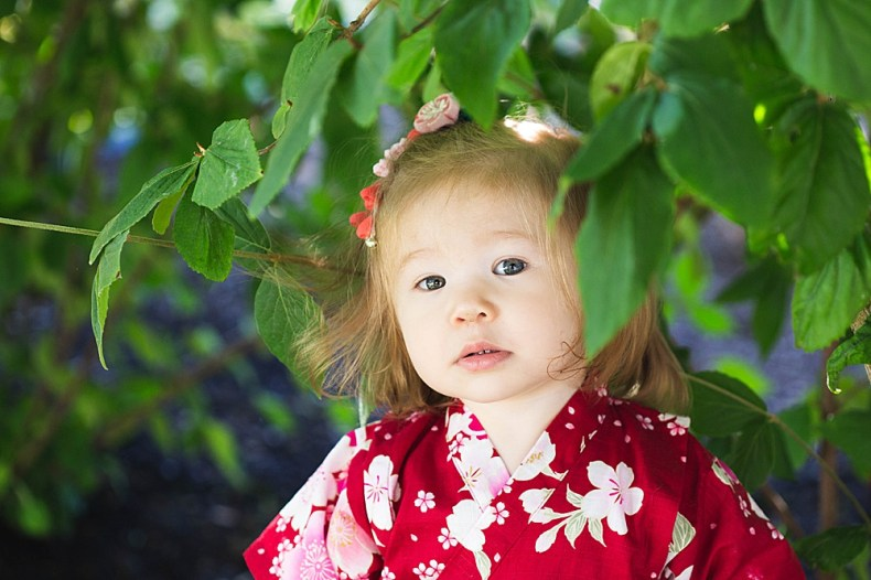 Asian girl peeking out of leaves. Photo by Belllingham photographer, Renee Bergeron.