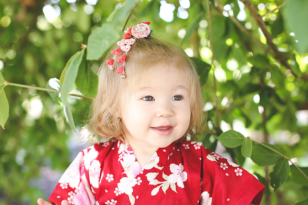 Umi peeking between leaves at her milestone session. Renee Bergeron. Little Earthling Photography.