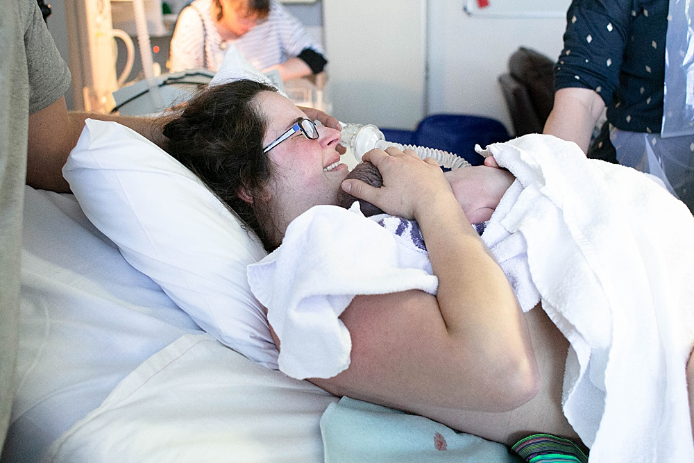 Mom holding her baby moments after a successful VBAC.