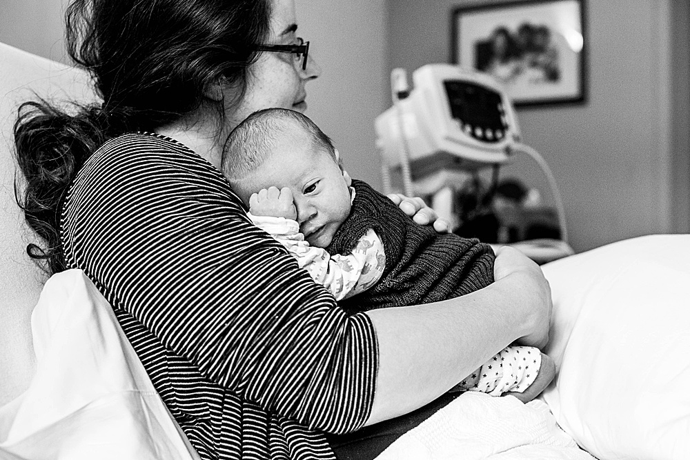 Newbor baby curled up with mom in hospital. Bellingham birth photographer.