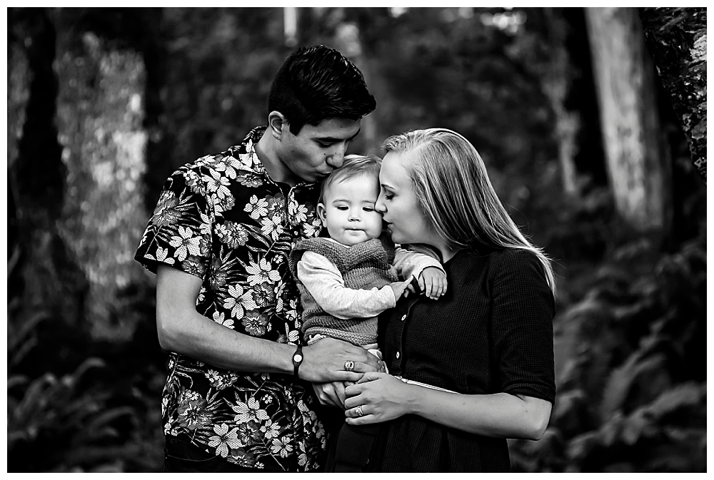 Black and white portrait of interracial couple kissing baby.