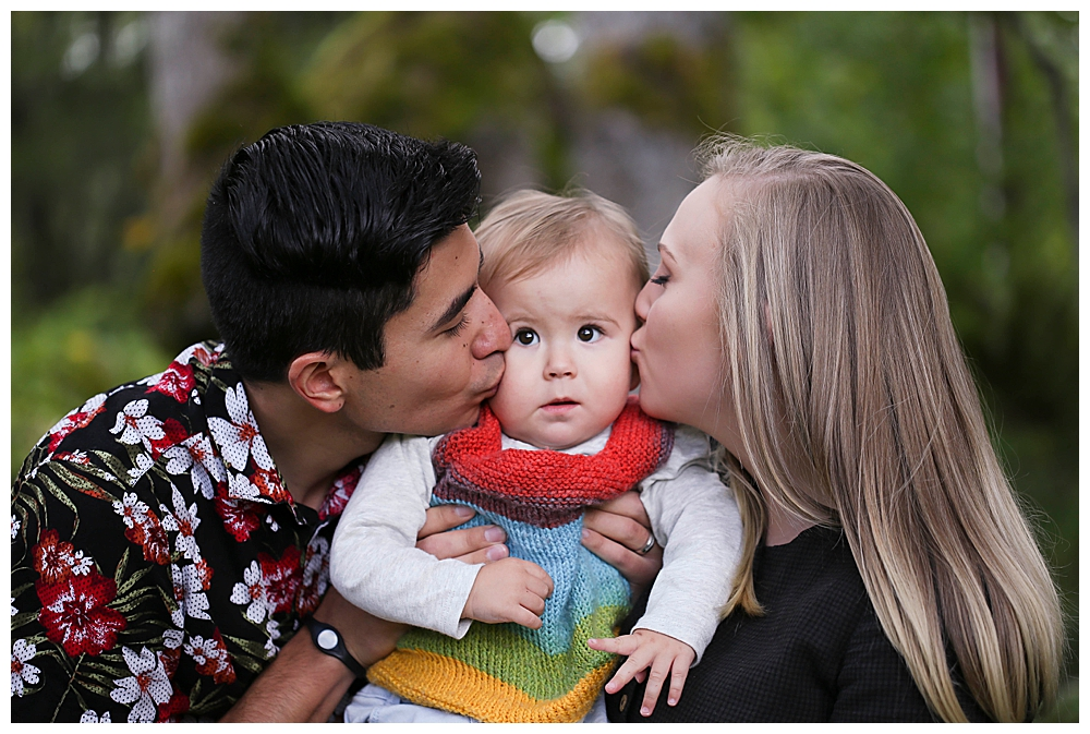 Mixed race couple kissing baby.