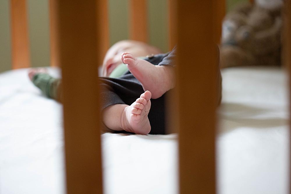 Newborn baby toes seen through crib.