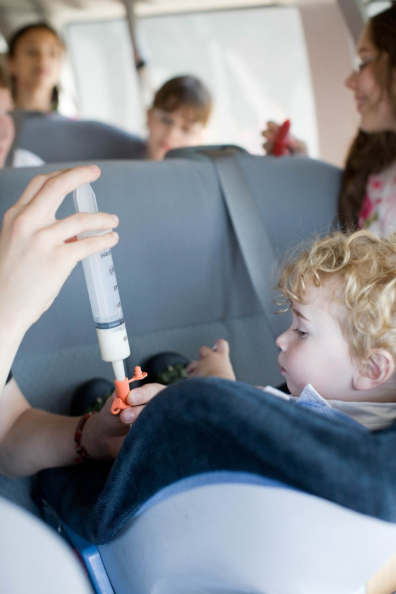 Toddler being tube fed while traveling in careseat.