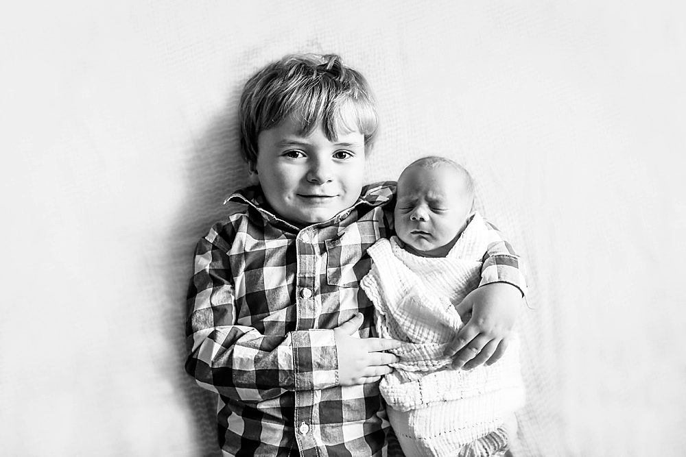Toddler and swaddled baby by Little Earthling Photography.