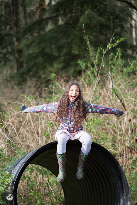 A girl in large rubber boots sitting on  a tunnel