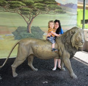 Esther and Noah sat on a lion statue at San Diego Zoo.