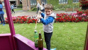 Noah plays hook a duck with plastic bottles in the beautiful campus.
