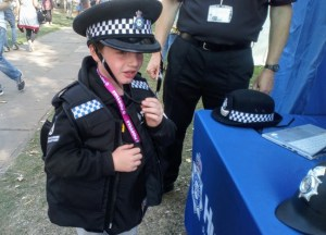 Noah dressed up in a police uniform, talking to representatives of Humberside Police.