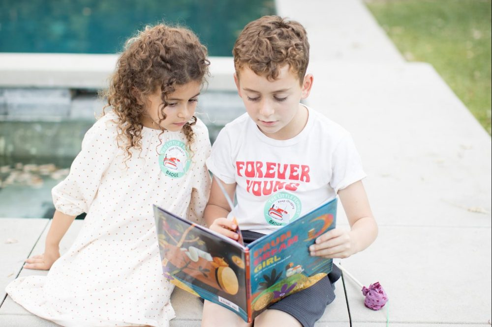 Boy and girl read The Little Feminist book club together