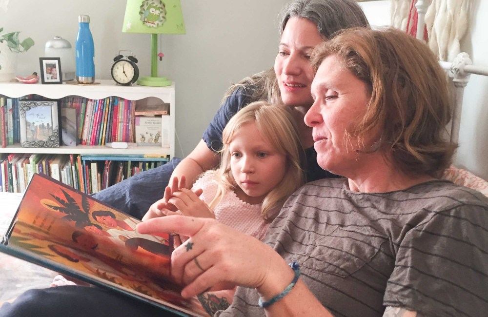family reading book about refugees