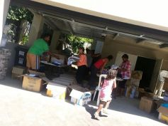 Volunteers sorting and packing clothing in T&T's garage