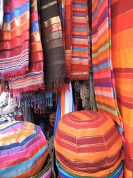 Colourfully striped Throws & poufs of an Essaouira market stall