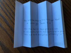 Photo of folded paper with verses written