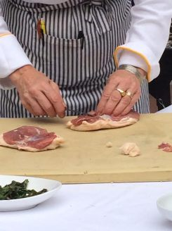 The chef demonstrates how to remove the extra fat from the duck breasts