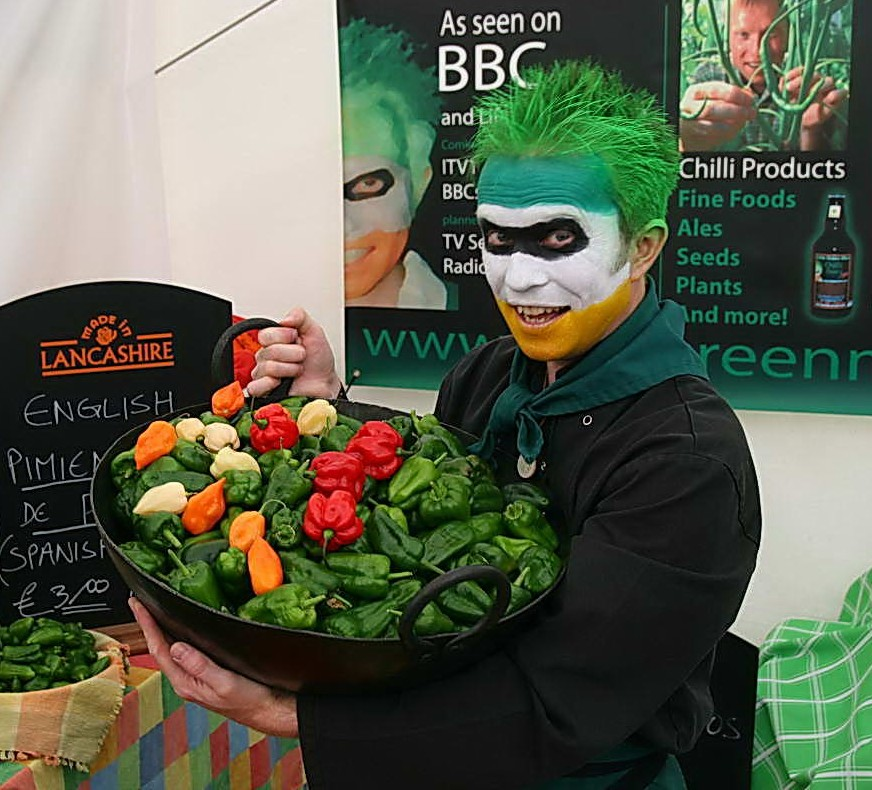 Chilli Rich from Little Green Men Chilli Lancashire holding a karai pan full of chilis in his chilliman makeup, green chilli hair and chefs outfit