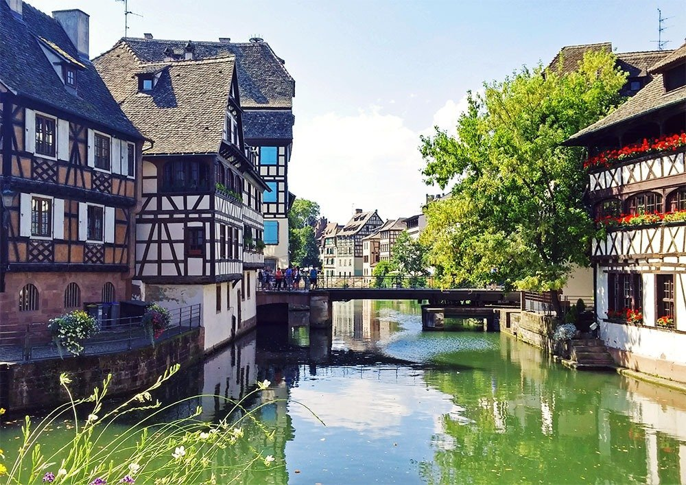 Strasbourg travel guide - Begin your fairytale holiday in Petite France – the most enchanting place in Strasbourg. Stroll along the banks of the quiet River Ill past pastel houses and flower-decked bridges and take a thousand photos, relish the scene, and enjoy good food and wine.