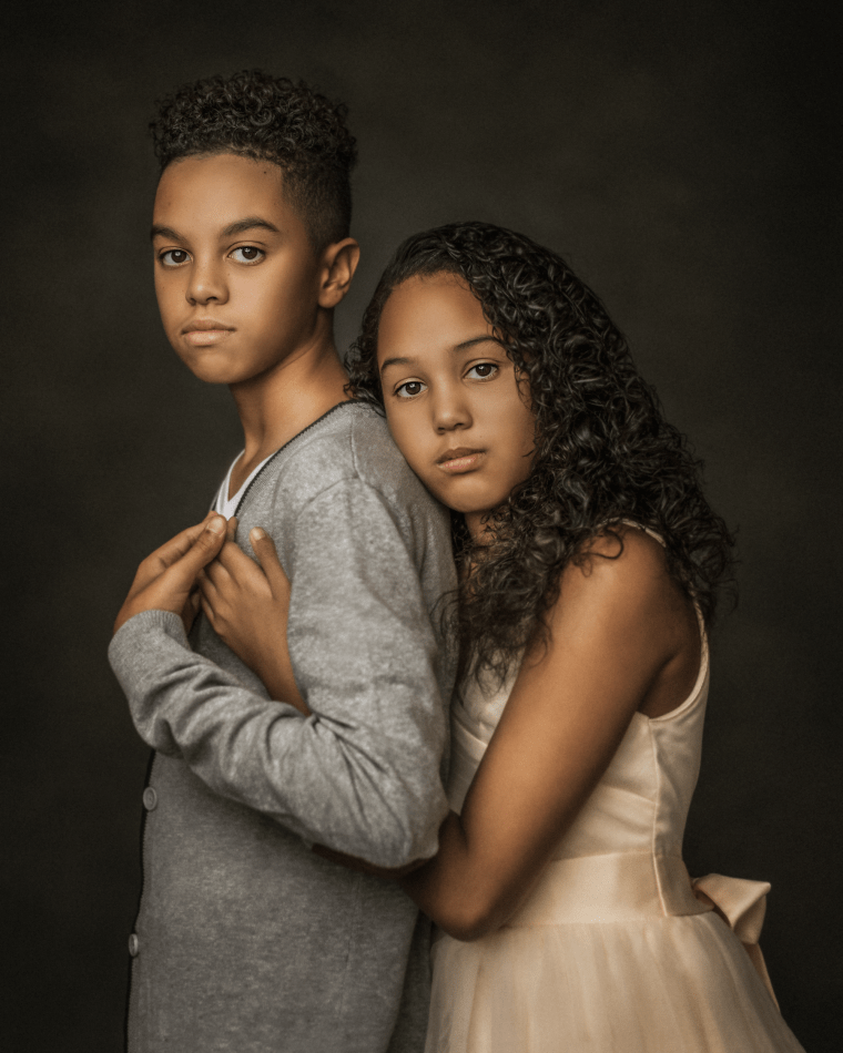 a brother and sister hugging each other during a family photo session