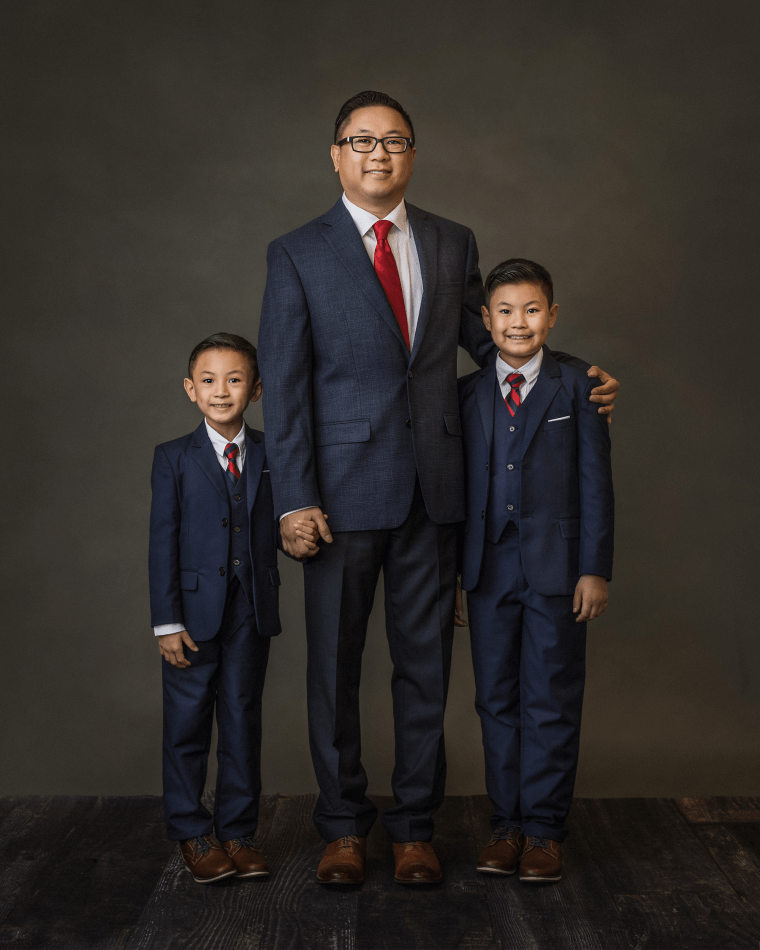 a father and his two sons all wearing blue suits during a family photo session