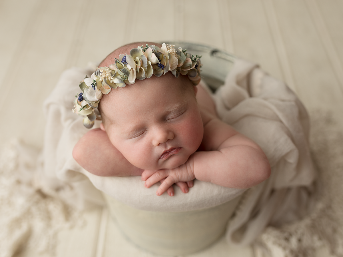 a one week old newborn baby wearing a floral bonnet during her newborn photo session