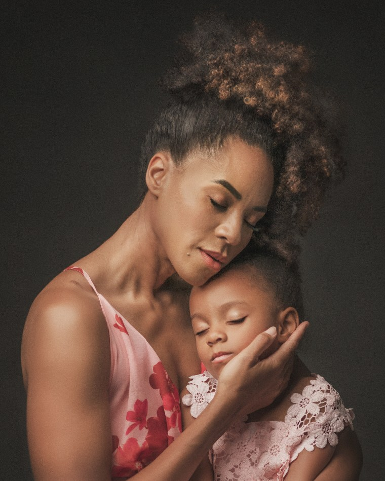 A mother embracing her four year old daughter