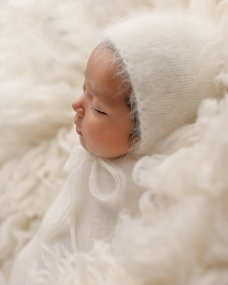 a three day old newborn baby wearing a cream colored bonnet