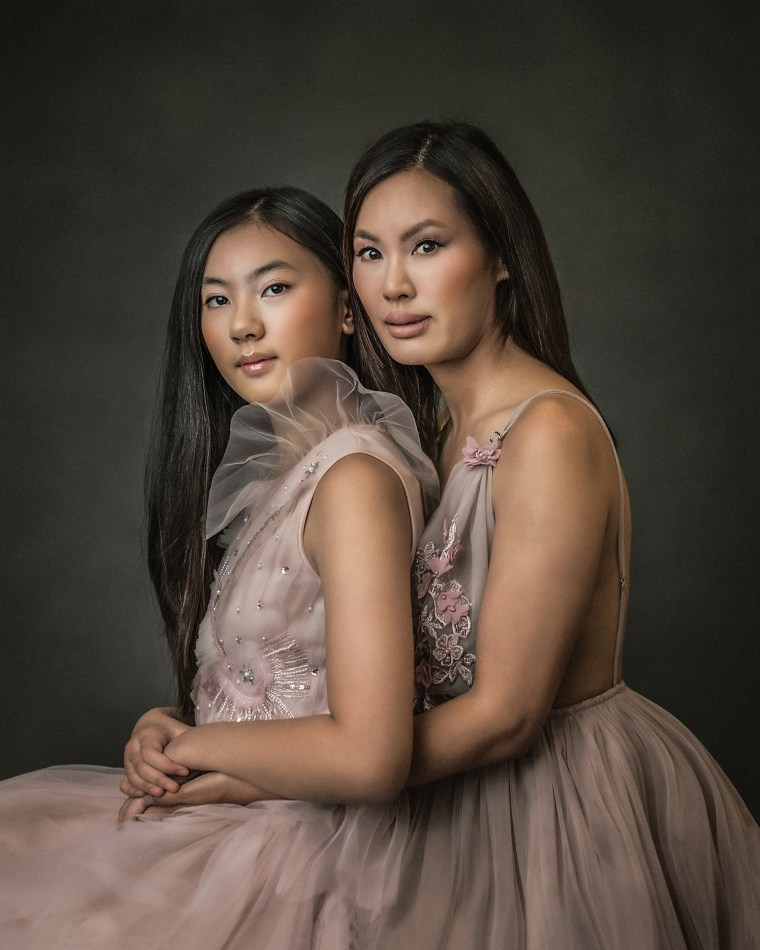 a mother and daughter wearing pink tulle and lace dresses and embracing
