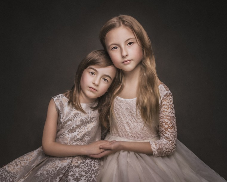 two young sisters wearing ivory and gold dresses and embracing each other