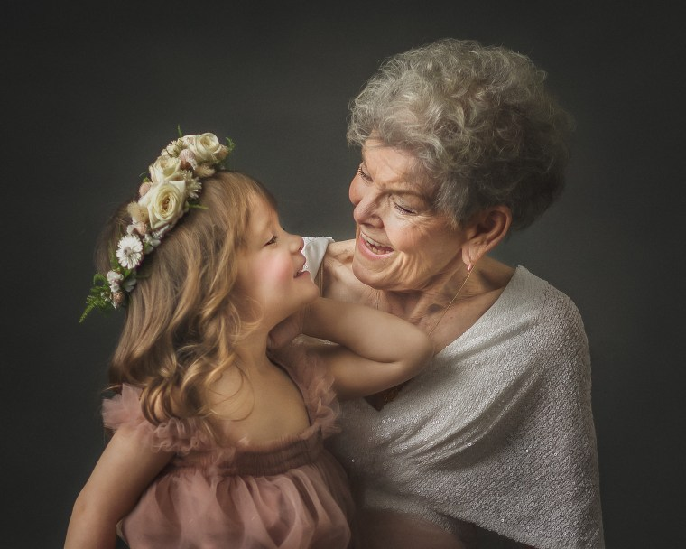A 92 year old woman embracing her great granddaughter