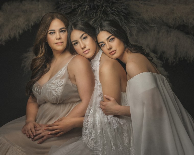 A mother wearing an ivory tulle and floral dress embracing her two daughters