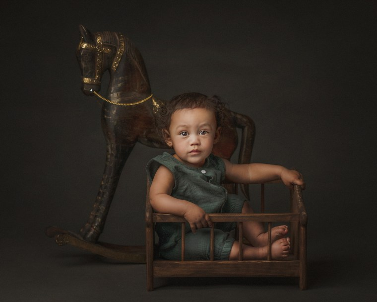 a 6 month old baby wearing a green romper while sitting in a wood cradle