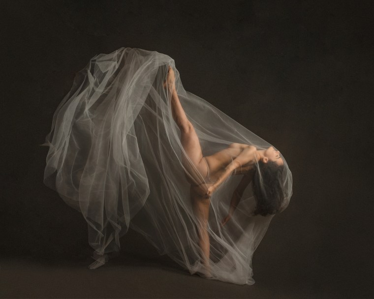 a woman covered in tulle while kicking high into the air